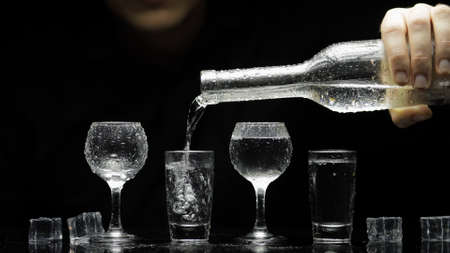 Bartender pouring up frozen vodka from a bottle into four shots glasses with ice cubes against black background. Barman pour of clear transparent alcohol drink rum tequila in shot-glass