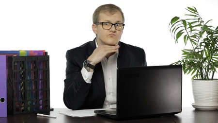Handsome businessman manager at working desk in office shows that he already has a lot of work. Hand near neck. Business people. Emotions. Guy in suit, shirt, glasses. White background 版權商用圖片