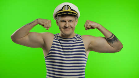 Young muscular sailor man shows muscles looking at camera. Seaman guy smiling in sailors vest. Striped navy white and blue shirt, captain nautical hat. Isolated on chroma key background Zdjęcie Seryjne
