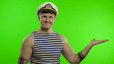 Young muscular sailor man pointing to something with hands. Seaman guy smiling in sailors vest. Striped navy white and blue shirt, captain nautical hat. Isolated on chroma key background