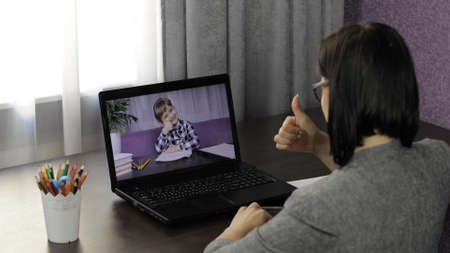 Woman teacher looking at laptop web camera making video call with little school girl pupil. Working from home. Distance education with children online class for kids on internet. Webcam e-learning Stock Photo