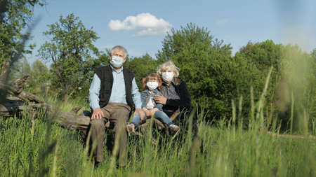 Grandparents with granddaughter together sitting in spring park in medical masks. Coronavirus covid-19 pandemia quarantine. Family time together. Grandfather, grandmother, girl child sitting together Banque d'images