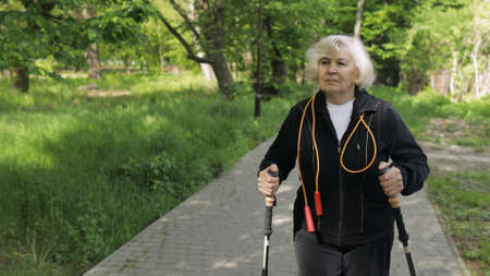 Active senior elderly 80 years old caucasian woman training Nordic walking with ski trekking poles in park. Natural green tree background. Active leisure. Hiking woman. Old people healthy lifestyle Фото со стока