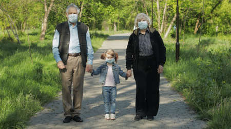 Old grandparents with granddaughter together walk in spring park in medical masks. Coronavirus covid-19 pandemia quarantine. Family time together. Grandfather, grandmother, girl child holding hands