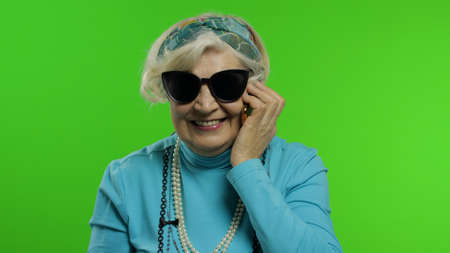 Elderly stylish granny caucasian mature woman emotionally talking on mobile phone. Chroma key background. Trendy old grandmother with smartphone in retirement age in fashion clothes. Senior people