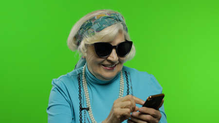 Elderly stylish granny caucasian mature woman using social media app on smartphone successful smiling thumbs up. Chroma key background. Old grandmother make online shopping on mobile phone