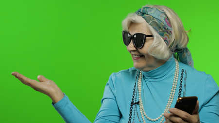 Elderly stylish grandmother caucasian mature woman using smartphone and pointing at something with hand. Show thumbs up. Chroma key background. Old granny in fashion clothes browsing on mobile phone Imagens