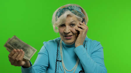 Elderly stylish granny caucasian mature woman emotionally talking on mobile phone and show money banknotes. Chroma key background. Old grandmother with smartphone in fashion clothes. Senior people
