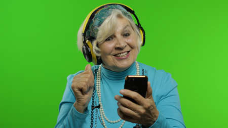 Elderly style granny caucasian mature woman in headphones dancing, listen music from smartphone app on chroma key background. Senior old grandmother in fashion clothing celebrates Imagens