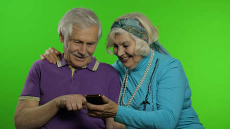 Elderly mature retired couple holding smartphone looking at mobile phone screen using social media app. Chroma key background. Senior old grandparents family having fun enjoy online shopping, news