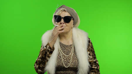 Elderly style granny caucasian mature woman in sunglasses posing, smoke cigarette on chroma key background. Trendy old grandmother in retirement age in fashion leopard clothes. Senior people