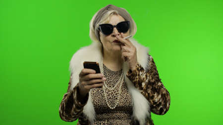 Elderly stylish granny caucasian mature woman in sunglasses using smartphone, smoke cigarette. Chroma key background. Trendy old grandmother in retirement age. Fashion leopard clothes. Fashion people Imagens