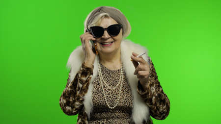 Elderly stylish granny caucasian mature woman emotionally talking on mobile phone. Chroma key background. Trendy old grandmother with smartphone in retirement age in fashion clothing. Senior people
