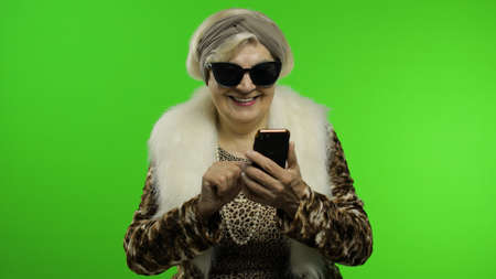Elderly stylish granny caucasian mature woman in sunglasses using social media app on smartphone. Chroma key background. Trendy old grandmother in retirement age in fashion clothing. Senior people