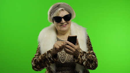 Elderly stylish granny caucasian mature woman in sunglasses using social media app on smartphone. Chroma key background. Trendy old grandmother in retirement age in fashion wearing. Senior people Imagens