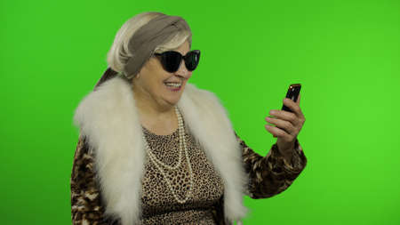 Elderly stylish granny caucasian mature woman using app on smartphone for video call. Chroma key background. Old grandmother in fashion wearing talking on mobile phone making conference. Senior people