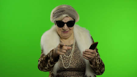 Elderly stylish grandmother caucasian mature woman using smartphone and pointing at camera with hand. Chroma key background. Old granny in fashion wearing browsing on mobile phone. Senior people Imagens