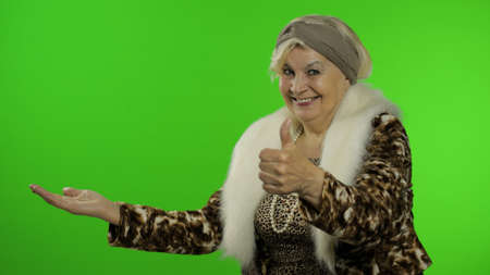 Elderly style granny caucasian mature woman pointing at something with hand on chroma key background. Trendy senior old grandmother in retirement age in fashion leopard clothes smiling. Green screen