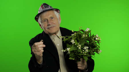 Elderly stylish grandfather caucasian mature man with bouquet of flowers and an engagement ring on chroma key background. Old senior grandparent in fashion clothes goes on date with wife. Green screen
