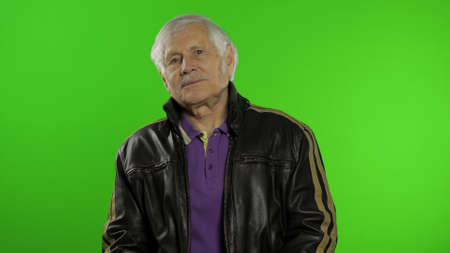 Elderly stylish grandfather caucasian rocker and biker mature man on chroma key background. Old senior grandparent in fashion leather jacket. Green screen Imagens