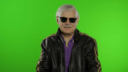 Elderly stylish grandfather caucasian rocker and biker mature man in sunglasses on chroma key background. Old senior grandparent in fashion leather jacket. Green screen