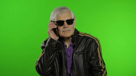 Elderly stylish grandfather caucasian mature rocker and biker man talking on smartphone. Chroma key background. Old grandparent in fashion leather jacket. Technology for seniors people