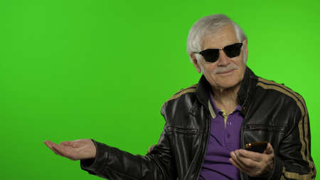Elderly stylish grandfather caucasian mature biker man using smartphone, pointing at something with hand. Chroma key background. Old grandparent in fashion clothes. Technology for seniors people Imagens
