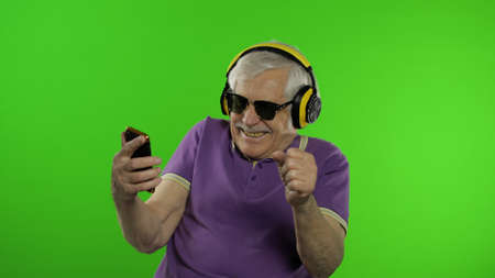 Elderly stylish grandfather caucasian mature man using social media app on smartphone smiling laughs cheerfully. Chroma key background. Old senior grandparent in sunglasses browsing on mobile phone