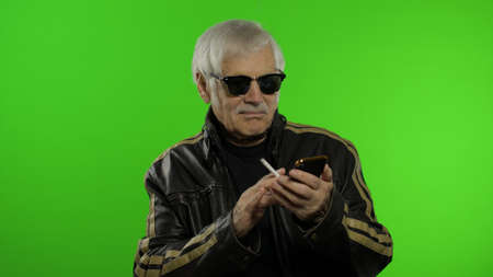 Elderly stylish grandfather caucasian mature rocker and biker man using app on smartphone for online shopping. Chroma key background. Old senior grandparent in leather jacket browsing on mobile phone