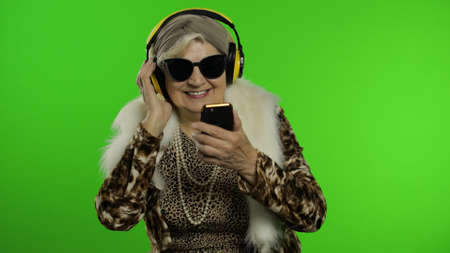 Elderly style granny caucasian mature woman in sunglasses and headphones dancing listen music from smartphone app on chroma key background. Senior old grandmother in fashion leopard clothes celebrates Imagens