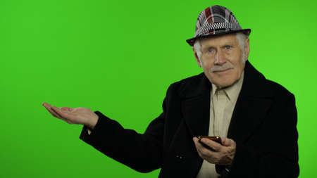 Elderly stylish grandfather caucasian mature man using smartphone, emotionally pointing at something with hand. Chroma key background. Old grandparent in fashion clothes. Technology for seniors people