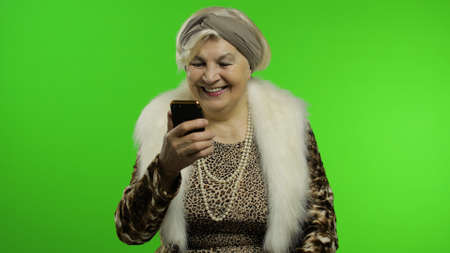 Elderly stylish granny caucasian mature woman using app on smartphone for successful online shopping. Chroma key background. Old grandmother in fashion wearing browsing on cell phone. Senior people
