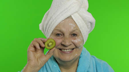 Adult senior caucasian woman grandmother in bathrobe and towel over head having fun with kiwi while applying moisturizing cream. Chroma key background. Beauty procedures for mature grandparents people Stock Photo