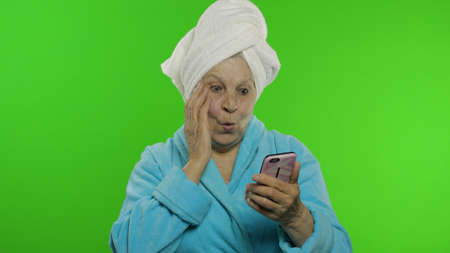 Adult senior caucasian woman grandmother in bathrobe and towel over head using app on smartphone for online shopping, smiling. Chroma key background. Skin procedures for mature grandparents people