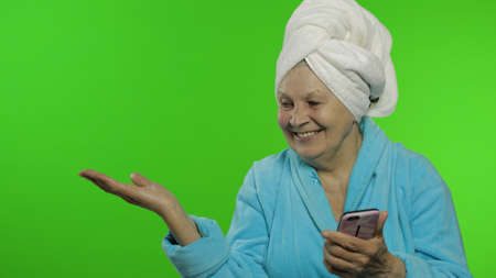 Adult senior caucasian woman grandmother in bathrobe and towel over head using smartphone, pointing at something with hand. Chroma key background. Skin beauty procedures for mature grandparents people