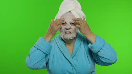 Adult senior caucasian woman grandmother in bathrobe and towel over head applying cosmetic fabric face mask. Chroma key background. Plastic skin care surgery procedures for mature grandparents people