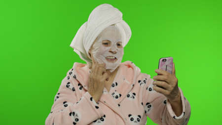 Adult senior caucasian woman grandmother in bathrobe and cosmetic fabric face mask on face making selfies using mobile phone. Chroma key background. Beauty procedures for mature grandparents people