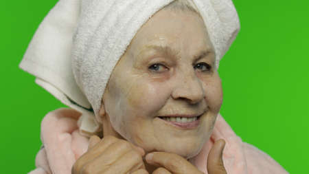 Adult senior caucasian woman grandmother in bathrobe and towel over head applying cosmetic bubble face mask. Chroma key background. Plastic skin care surgery procedures for mature grandparents people