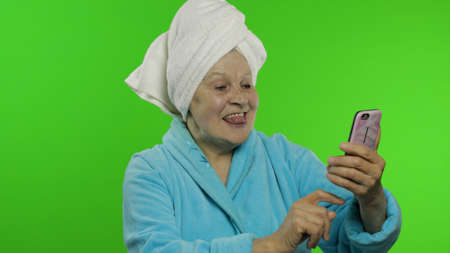 Adult senior caucasian woman grandmother in bathrobe and towel over head using smartphone social network app for video call. Chroma key background. Skin care procedures for mature grandparents people