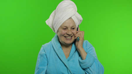 Adult senior caucasian woman grandmother in bathrobe and towel over head after shower talking on mobile phone. Chroma key background. Skin care procedures for mature grandparents people