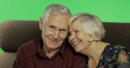 Senior aged man and woman sitting together on a sofa and smiles. Portrait. Chroma key background. Concept of a happy family in old age. Green screen background