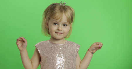 Girl in glossy dress. Little crown on the head. Happy, pretty little child, 3-4 year old blonde girl. Make faces and smile. Place for your logo or text. Green screen. Chroma Key