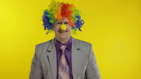 Successful clown manager office worker in wig and business suit at work. Guy businessman entrepreneur boss smiles, looks at camera. Copy space. Halloween. Yellow background