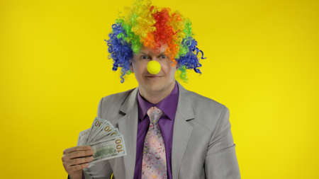 Happy clown manager office worker in wig and business suit with money banknotes dollar cash. Guy businessman entrepreneur boss smiles at work. Copy space. Halloween. Yellow background
