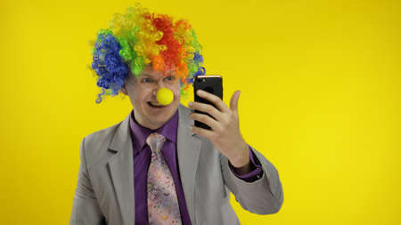 Happy clown director office worker in wig and business suit using app on smartphone in online work. Guy businessman entrepreneur boss smiles. Expressions. Copy space. Halloween. Yellow background Stock fotó
