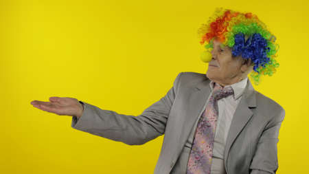 Senior clown manager office worker in wig and business suit at work pointing at something with hand. Guy businessman entrepreneur boss smiles, looks at camera. Copy space. Halloween. Yellow background Stock fotó