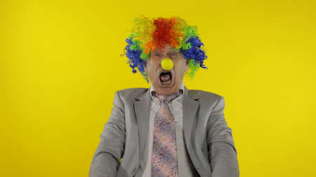 Senior clown manager office worker in wig and business suit at work making silly faces. Guy businessman entrepreneur boss smiles, looks at camera. Expressions. Copy space. Halloween. Yellow background Stock fotó