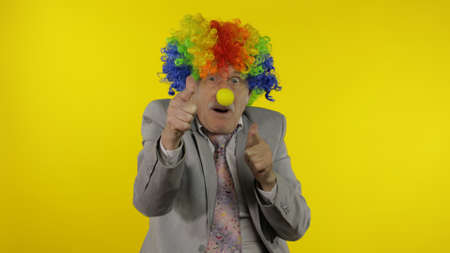 Senior clown manager office worker in wig and business suit at work making shot signs from hands. Guy businessman freelancer boss smiles. Expressions. Copy space. Halloween. Yellow background Stock fotó