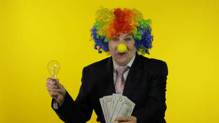 Elderly clown office worker in wig and business suit show light bulb. Concept of came up with good idea and receive money dollar cash banknotes income earnings. Businesswoman freelancer director