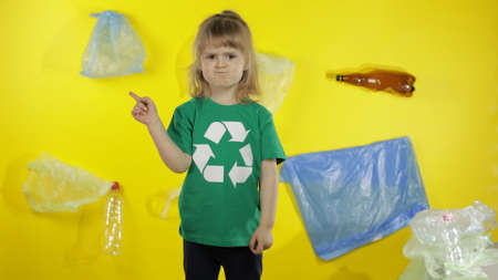 Girl activist volunteer in t-shirt with recycle logo asks not to litter. Background with bags, bottles. Save earth environment. Plastic trash nature pollution